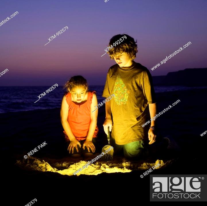 Stock Photo: An adventurous boy and girl find treasure after digging on a sandy beach.