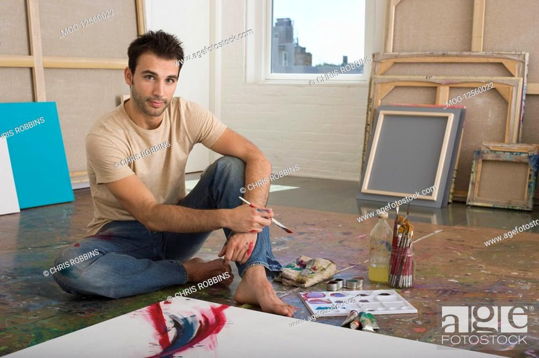 Stock Photo: Artist Working on Canvas on Floor of Studio.