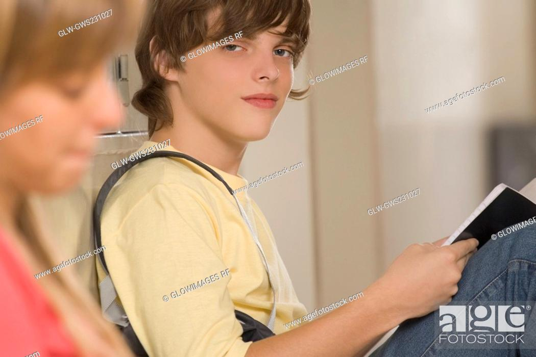 Stock Photo: Portrait of a teenage boy studying with his friend sitting beside her.