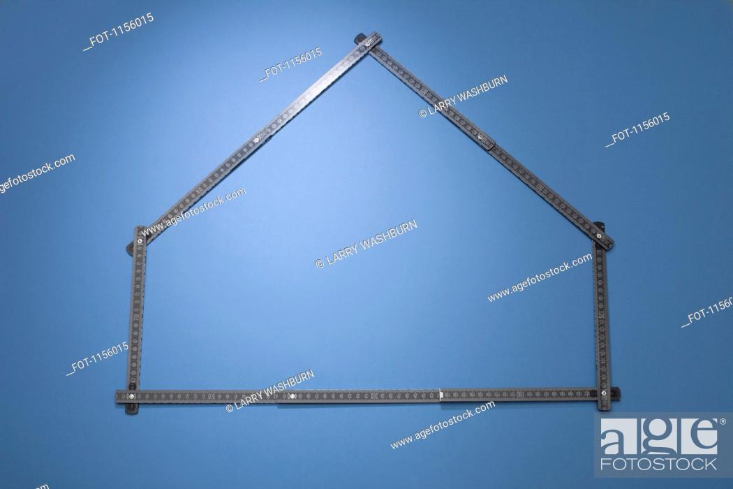 Stock Photo: A folding ruler arranged in the shape of a house.