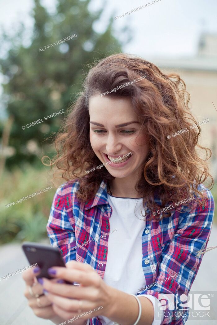 Stock Photo: Cheerful young woman using smartphone outdoors.