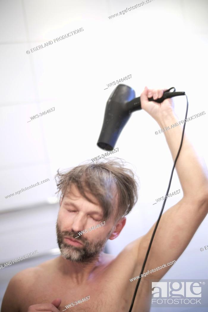 Stock Photo: Man using hair dryer.
