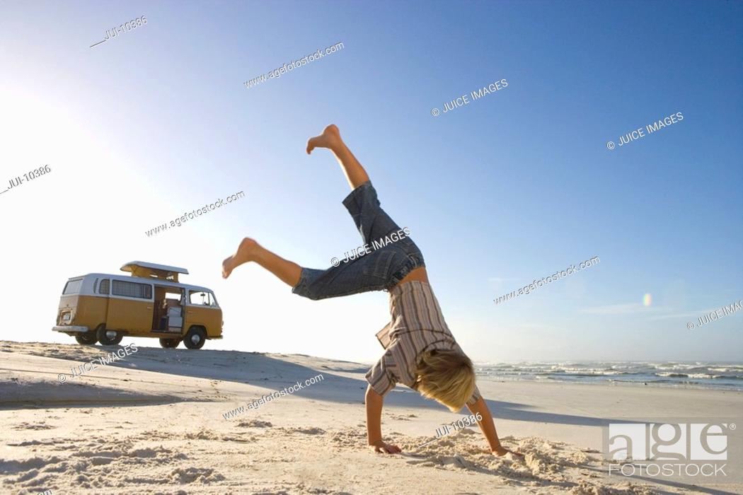 Stock Photo: Boy 6-8 performing cartwheel on beach, camper van in background, low angle view.