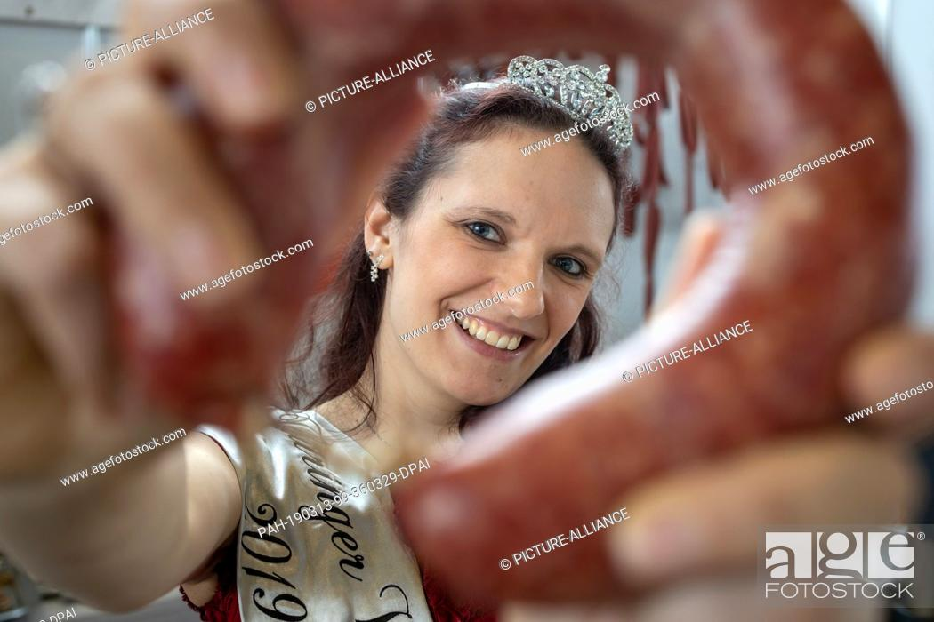 Stock Photo: 13 March 2019, Thuringia, Erfurt: The new sausage queen Jenifer Risch poses with a Kringel Knackwurst at the 23rd Day of Thuringian Sausage Specialities.