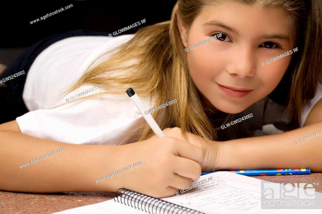 Stock Photo: Portrait of a girl writing on a textbook with a pencil.