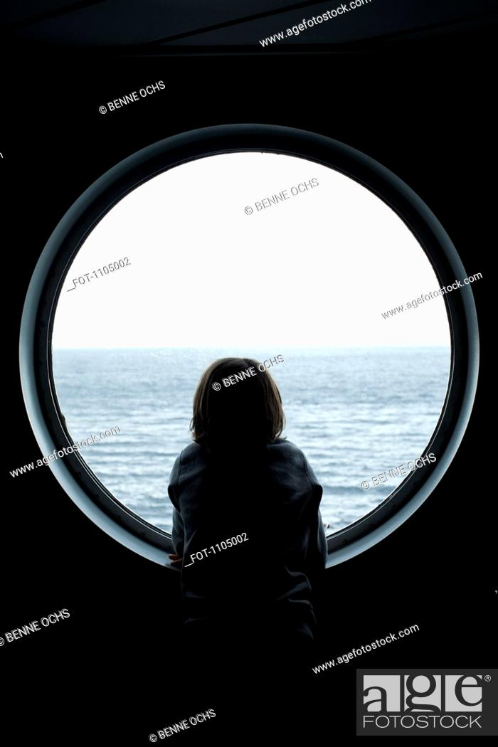 Stock Photo: Rear view of a boy looking through a porthole.