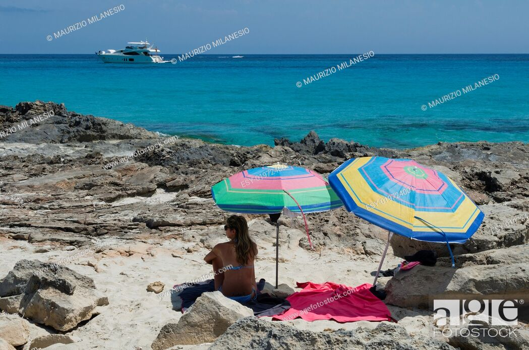 Stock Photo: Girl on the beach of sand and rocks sitting next to umbrellas observes speedboat off.