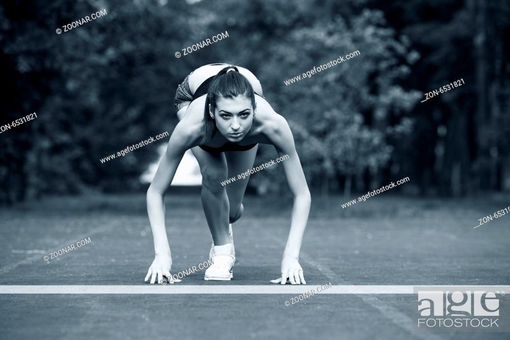 Imagen: Woman at start line ready to run.