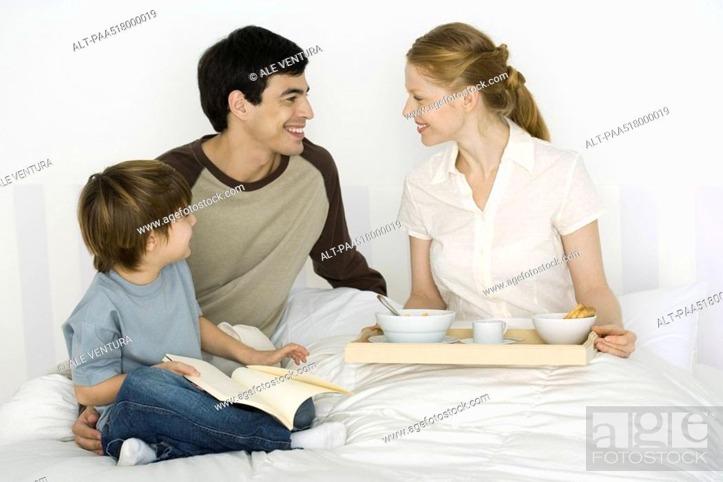 Stock Photo: Father and son giving mother breakfast in bed.