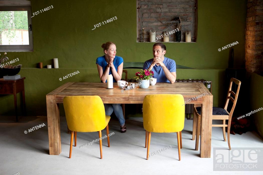 Stock Photo: A couple sitting at a dining table looking at each other uncertainly.