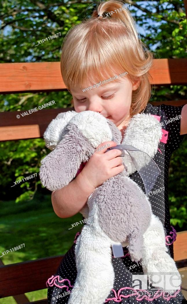 Stock Photo: This precious shot image shows a Caucasian 2 year old girl kissing her favorite stuffed animal, a white and gray plush dog You can tell by her facial expression.