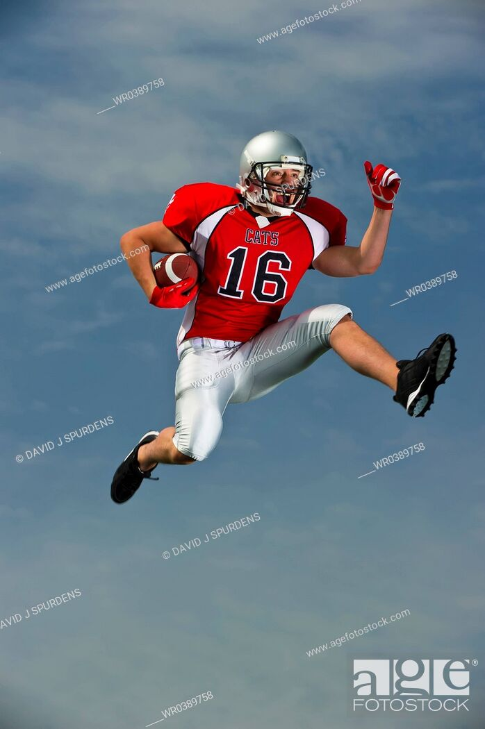 Stock Photo: American Football player ball under arm going for it.