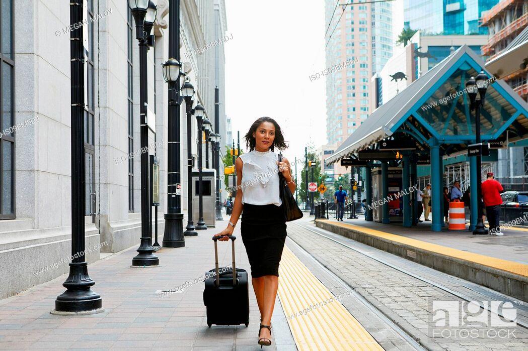 Stock Photo: Businesswoman pulling luggage alongside train.