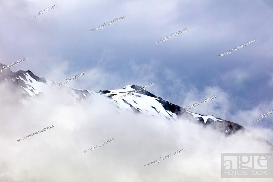 Stock Photo: Snow capped rugged rocky mountains in clouds on the Kenai Peninsula of Alaska.