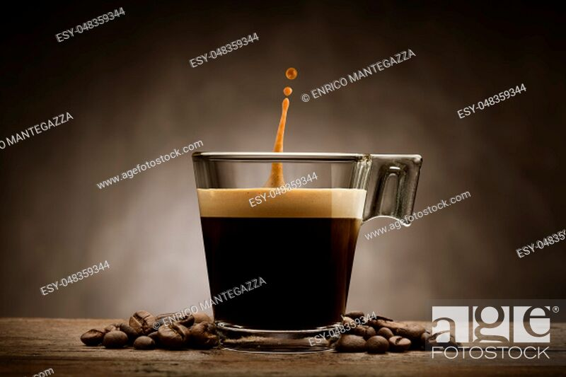 Stock Photo: Black coffee in glass cup with coffee beans and jumping drop, on wooden table.