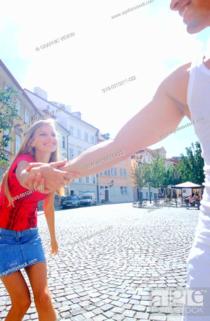 Stock Photo: Young man pulling young woman by her arm.