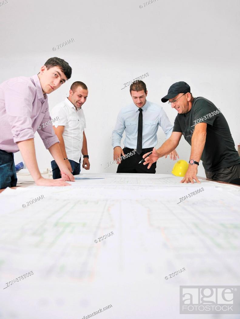 Stock Photo: Team of architects people in group on construciton site check documents and business workflow.