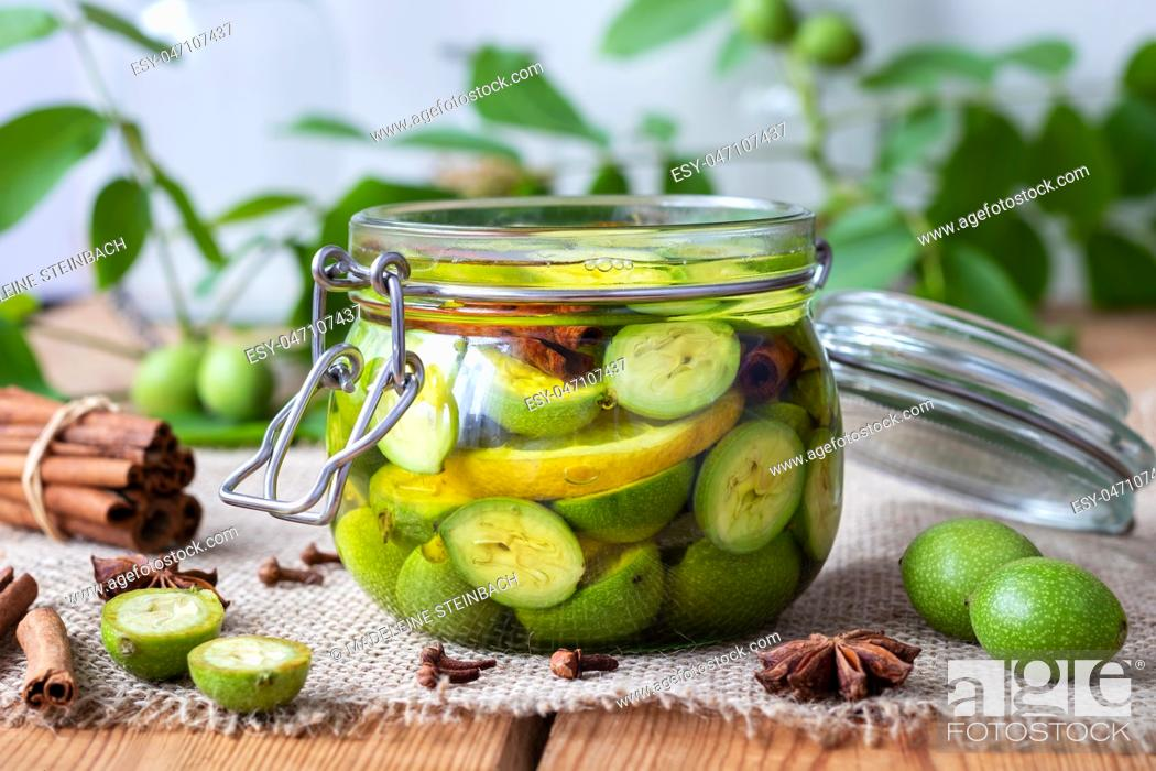 Stock Photo: Macerating unripe walnuts, lemon and spices in alcohol in a jar, to prepare homemade tincture.