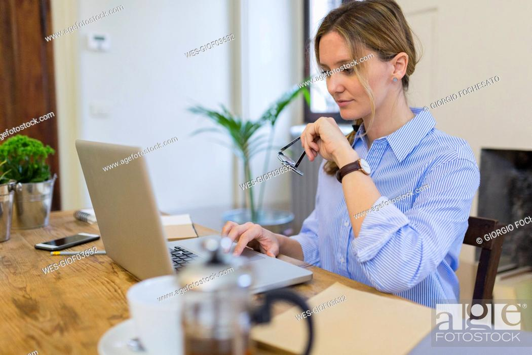 Stock Photo: Woman using laptop on wooden desk at home.