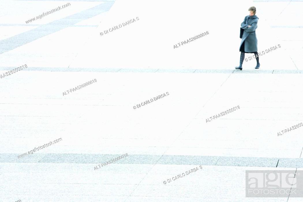 Stock Photo: Woman with arms folded walking across city square.