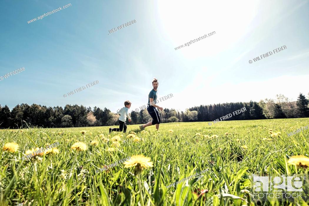 Stock Photo: Father and little son having fun together on a meadow in spring.