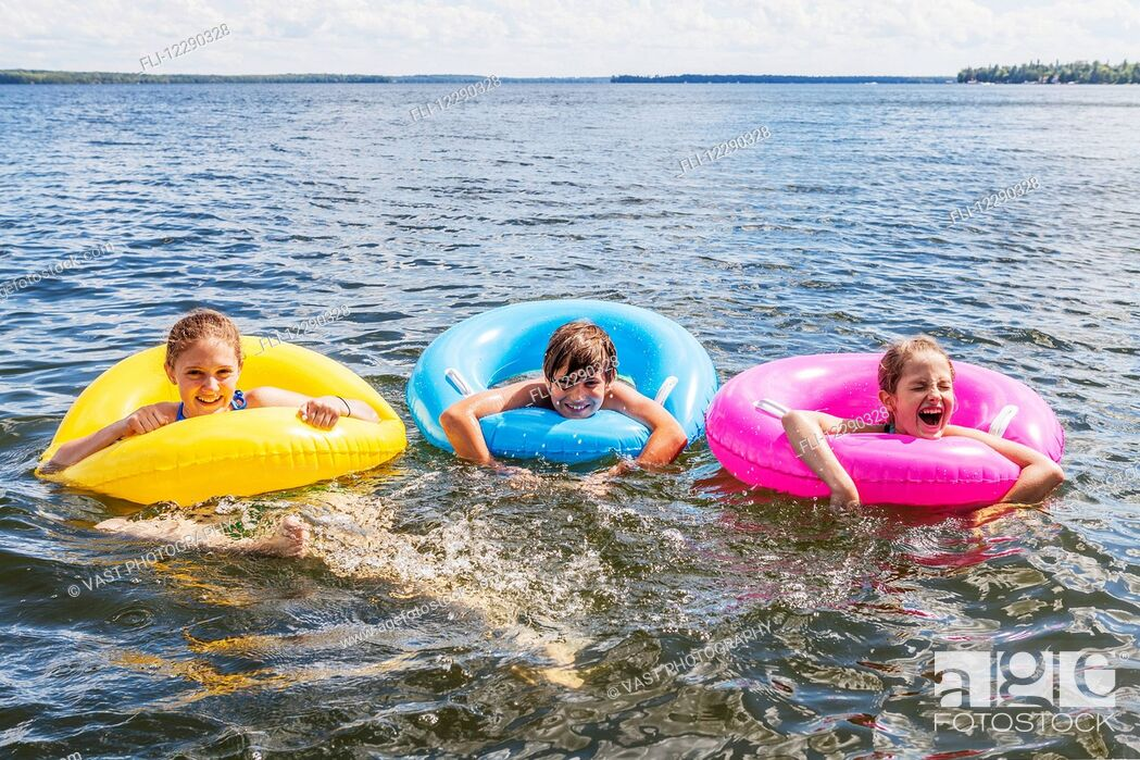 Stock Photo: Three kids playing in Balsam Lake wearing colorful inflatable rings; Ontario, Canada.