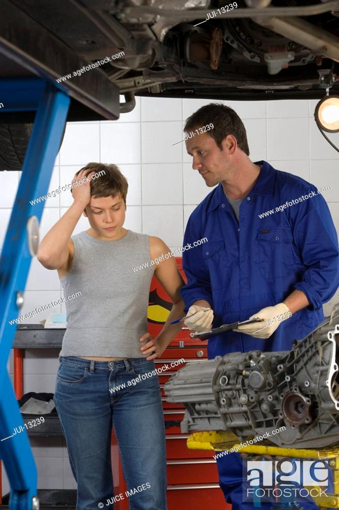 Stock Photo: Woman with hand to head by mechanic with clipboard by elevated car.