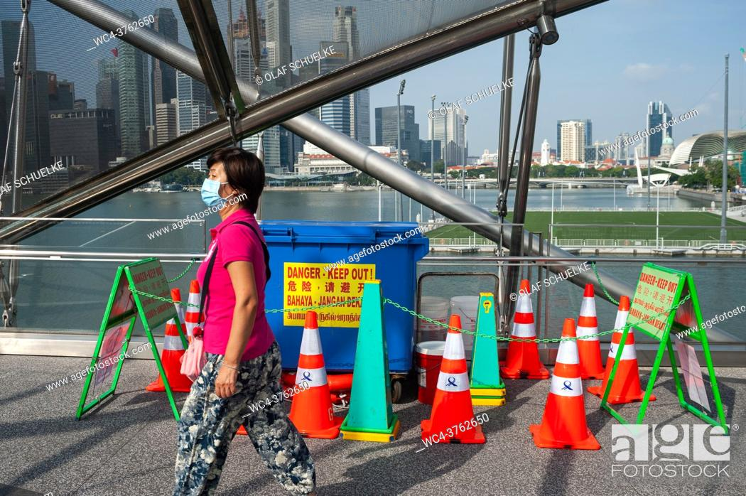Stock Photo: Singapore, Republic of Singapore, Asia - A woman wearing a compulsory protective face mask as a protection against the infectious coronavirus (Covid-19).
