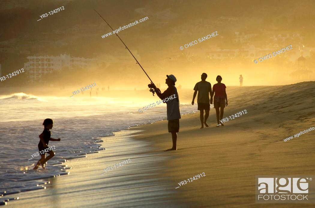 Stock Photo: A man fishes along a beach of resort hotels in San Jose del Cabo in Mexico's southern Baja California state.