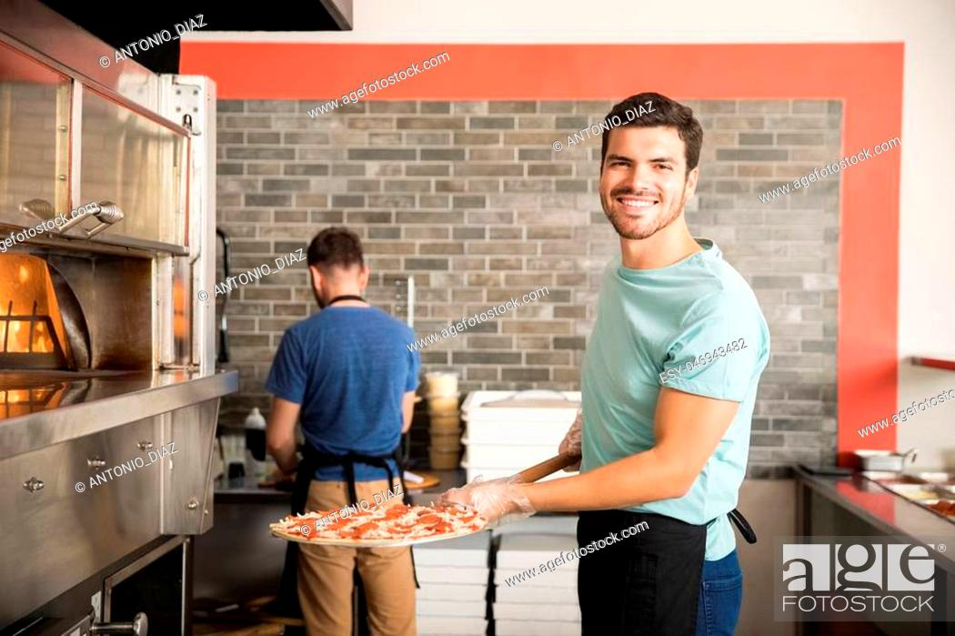 Stock Photo: Smiling chef in black apron putting pizza into the oven with peel at restaurant kitchen.
