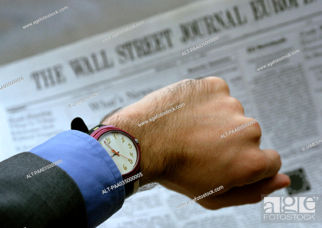 Stock Photo: Watch on wrist, newspaper in background.