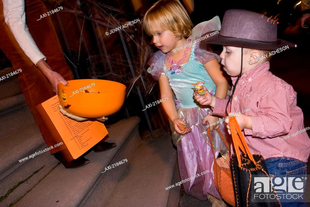 Stock Photo: USA, New York State, Children in Halloween costumes receiving sweets; New York City.