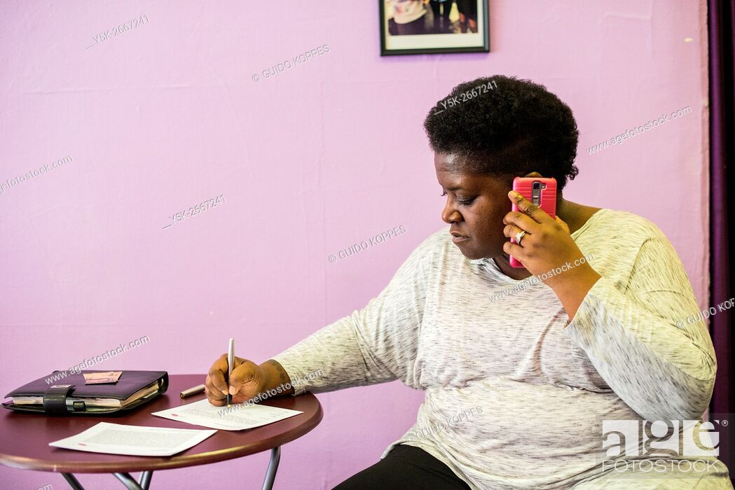 Stock Photo: Newark, New Jersey, USA. LGBTQ Community Center volunteer Tyett making a phone call with one of their visitors.