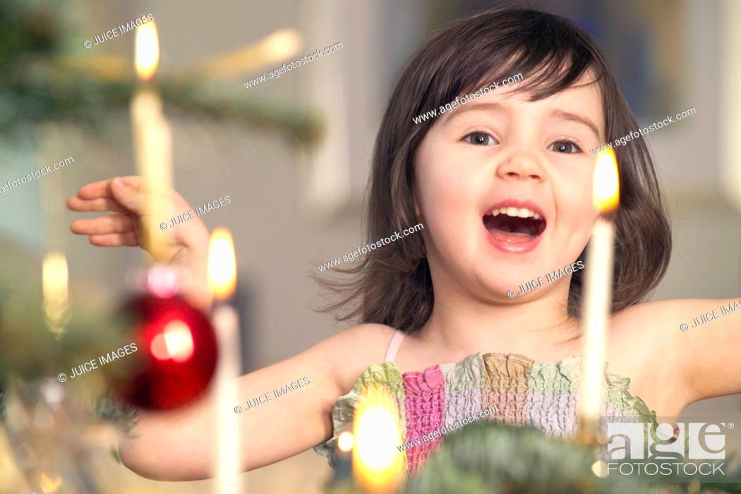 Stock Photo: Young girl singing next to Christmas tree.