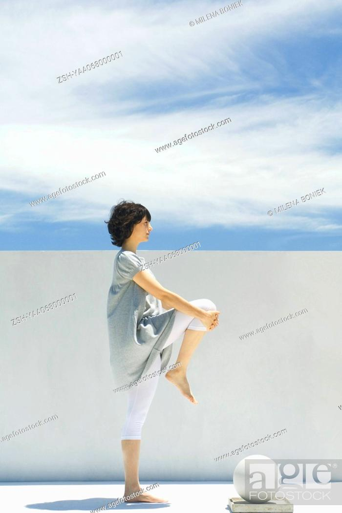 Stock Photo: Woman stretching outdoors, side view.