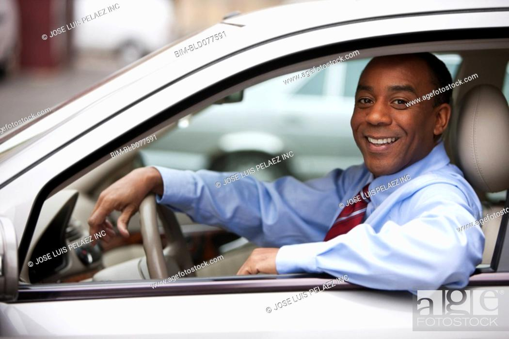 Stock Photo: African businessman driving car.