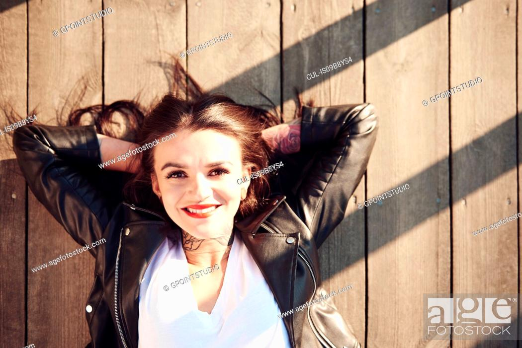 Stock Photo: Portrait of young woman lying on wooden decking, hands behind head, smiling, overhead view.