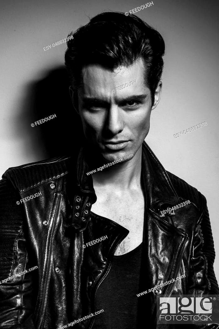 Stock Photo: black and white portrait of a young man in leather jacket posing in studio.