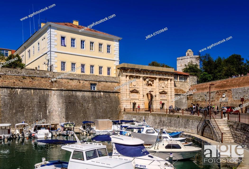 Stock Photo: Croatia, Dalmatia, Zadar, fishing port Fosa, city wall and Kopnena vrata / Landward Gate with Lion of Saint Mark.