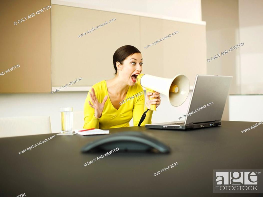 Stock Photo: Businesswoman yelling at laptop with bullhorn in conference room.