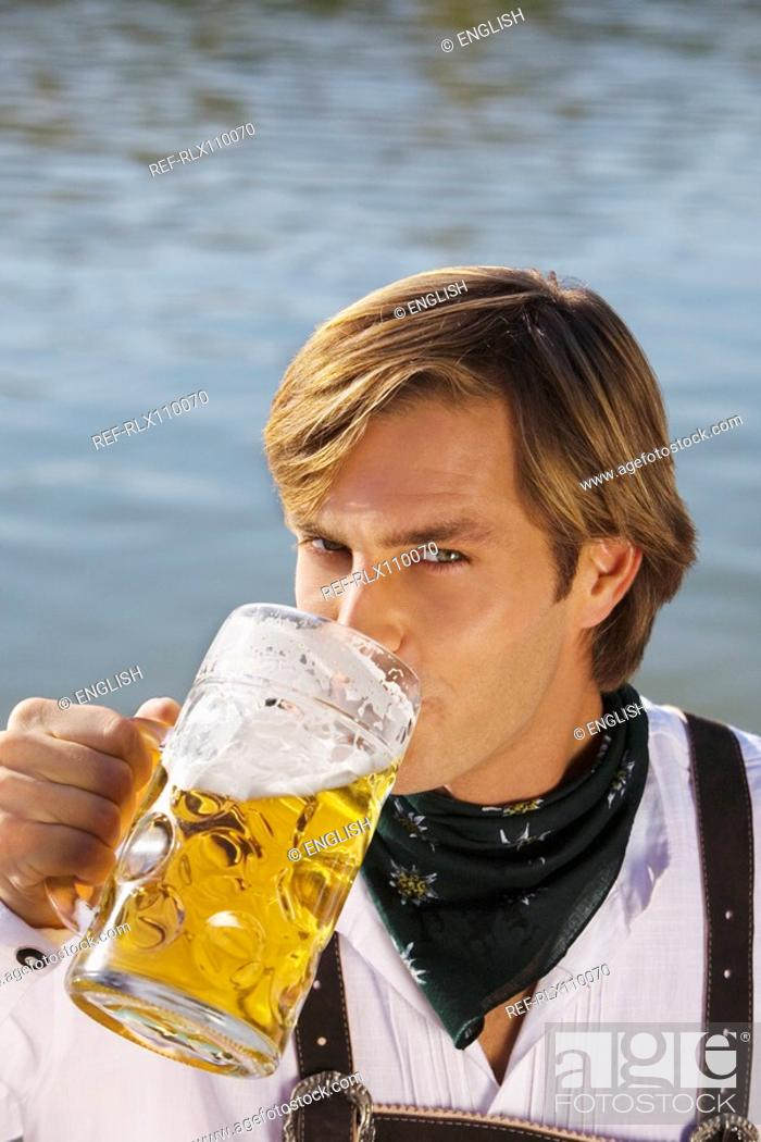 Stock Photo: Young man in traditional Bavarian outfit, drinking litre glass of beer, Munich.
