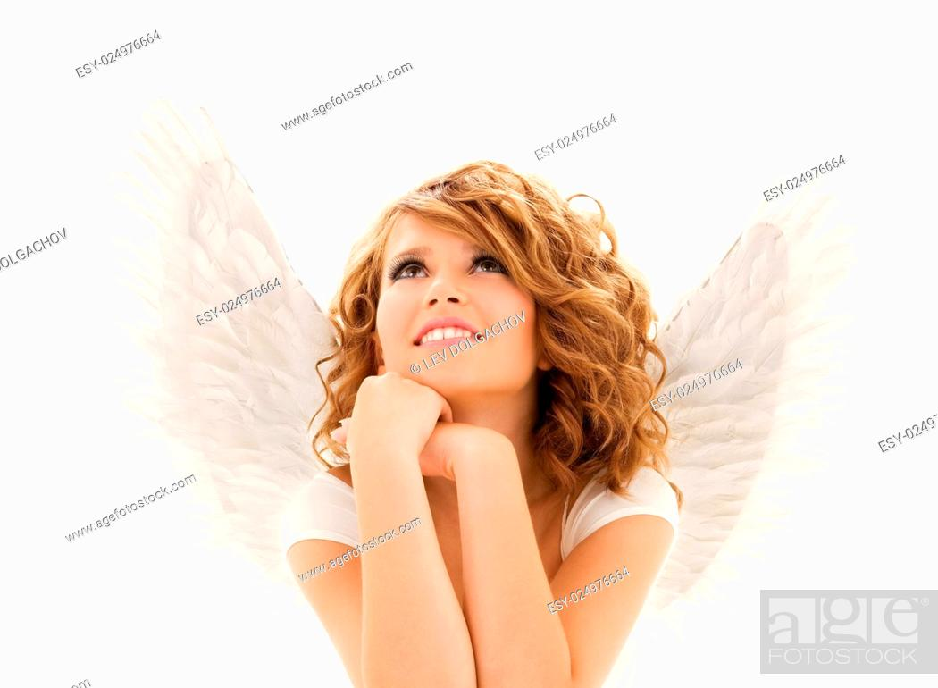 Stock Photo: people, holidays, christmas and religious concept - happy young woman or teen girl with angel wings over white background.