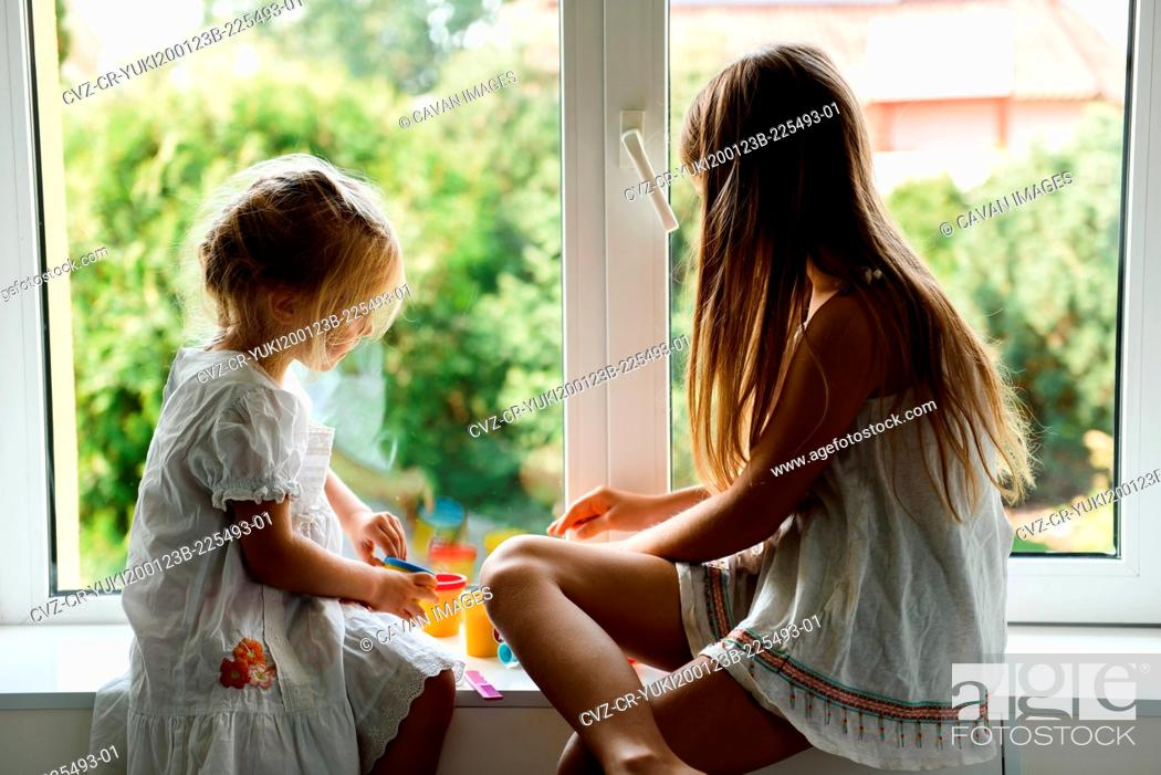 Stock Photo: Two sisters playing plasticine by the window.