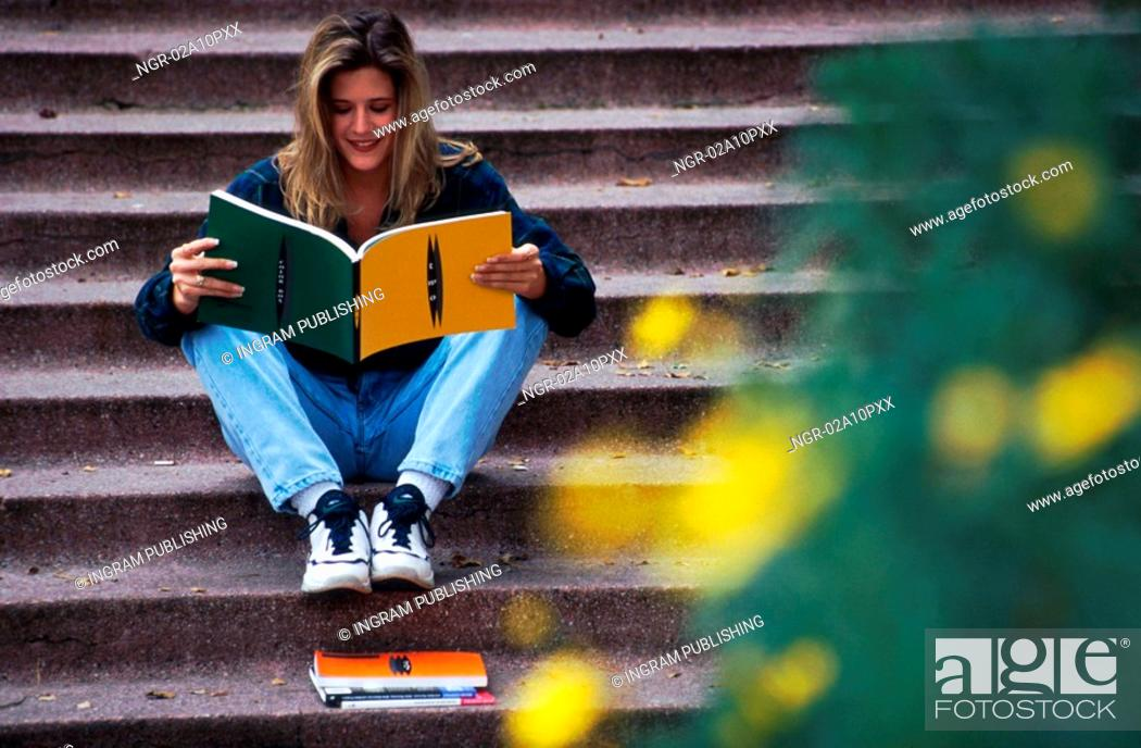 Stock Photo: woman sitting on steps and reading.