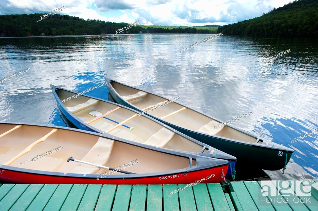 Stock Photo: Canoes at dock with blue sky reflecting in water in Bryant Pond, Maine.