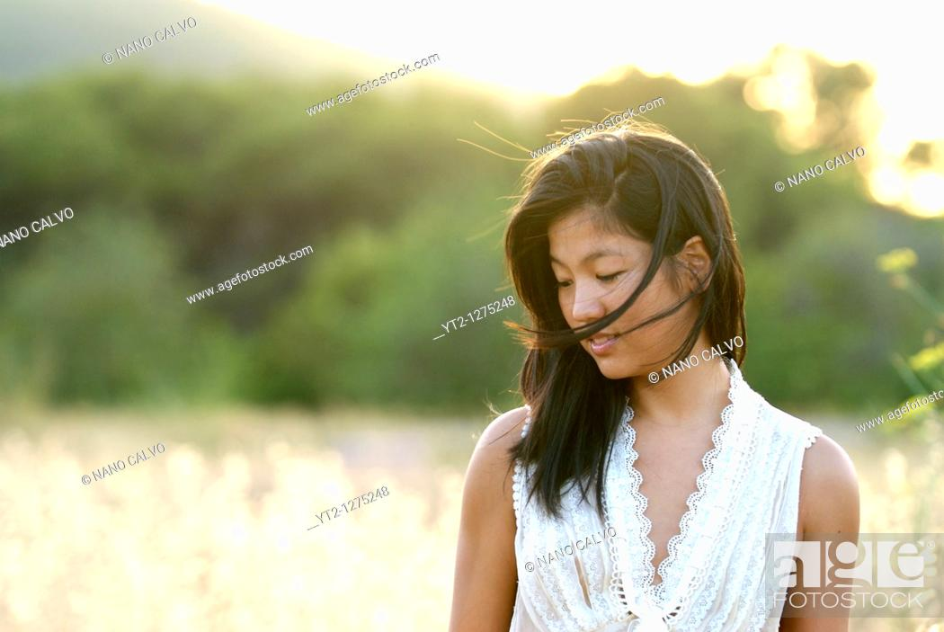 Stock Photo: Portrait of a cute young asian woman in a field, at sunset.