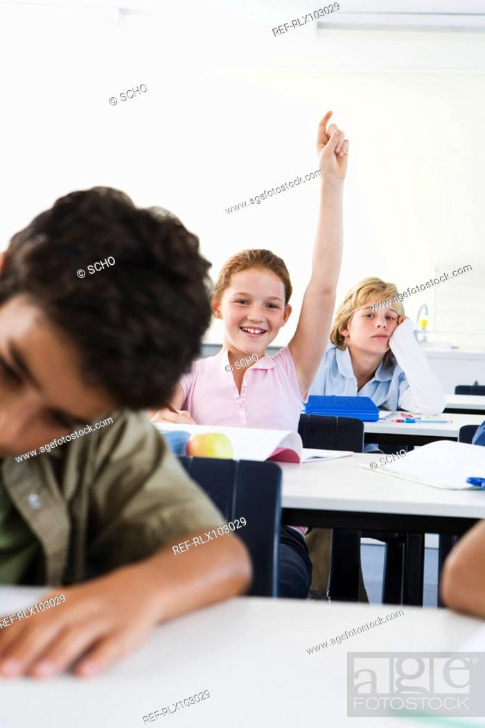 Stock Photo: Group of school children 10-13 in classroom with hand raised.