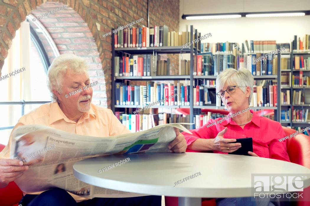 Stock Photo: Senior couple with newspaper and e-book in a city library.
