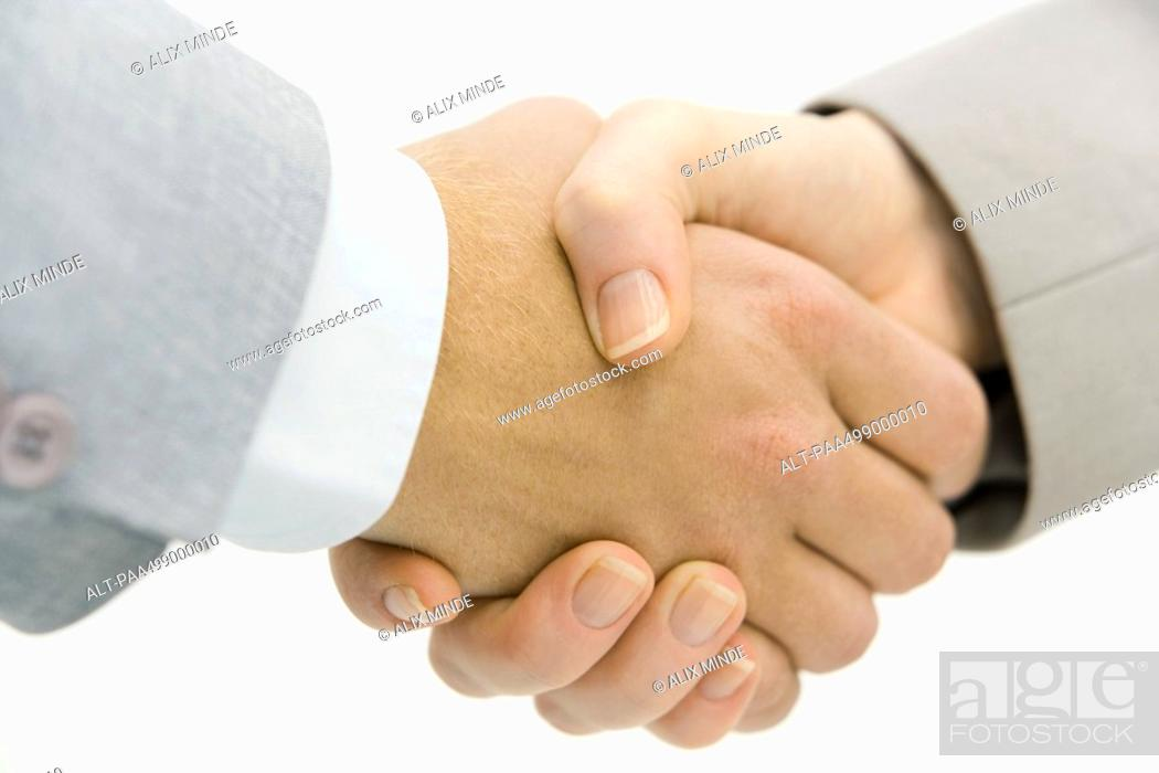 Stock Photo: Business partners shaking hands, cropped view, close-up.
