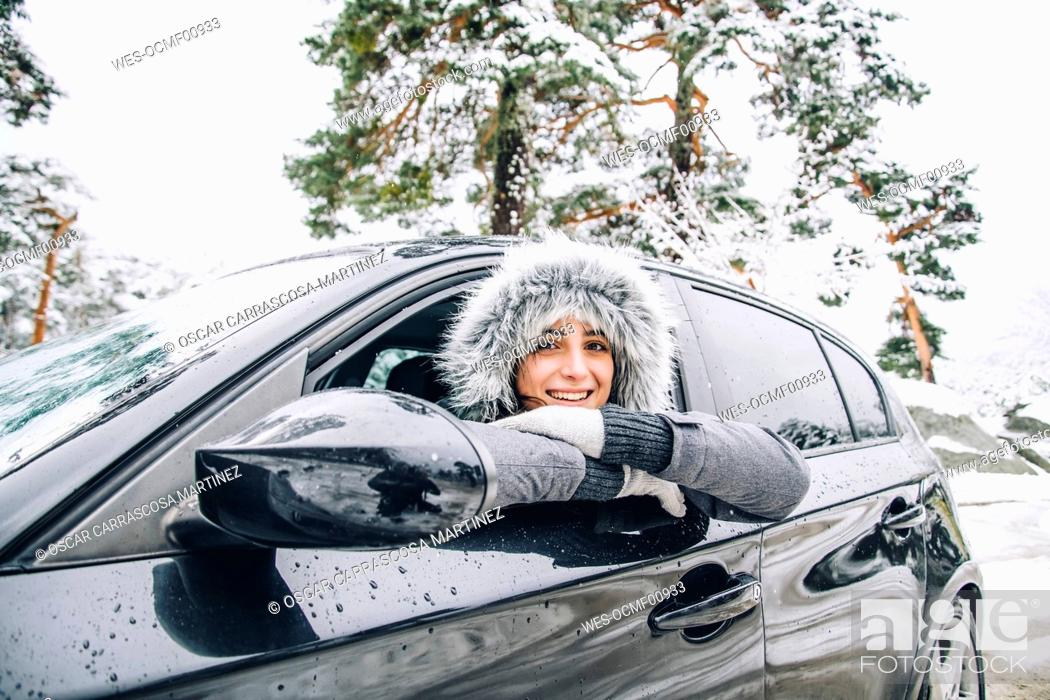 Stock Photo: Portrait of smiling young woman leaning out of car window in winter forest.
